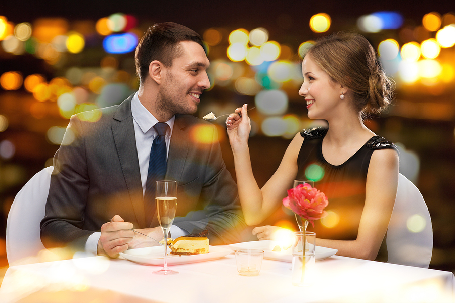 restaurant, couple and holiday concept - smiling couple eating d
